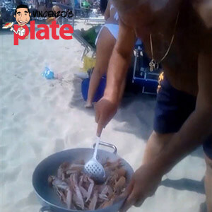 Chef Vincenzo cooking an Italian seafood recipe on the beach